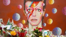 Flowers left at a mural of musician David Bowie.