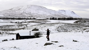 A man clears snows in Ingleborough near Hawes in Yorkshire