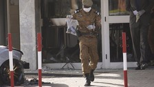 A policeman carries a bag full of personal items out of the bisieged hotel