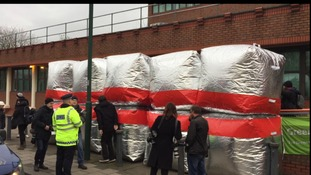The red line of inflatable barrages outside court.