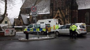 Forensic teams investigate after a body is found near a church hall