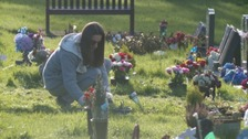 Woman laying flowers at grave