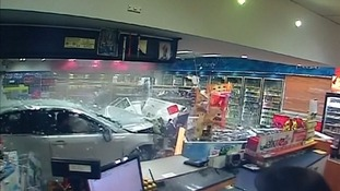 A car smashes through the front of the service station