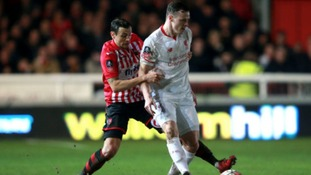 Exeter City's Alex Nicholls and Liverpool's Brad Smith (right) battle for the ball during the Emirates FA Cup, third round match at St James Park, Exeter.