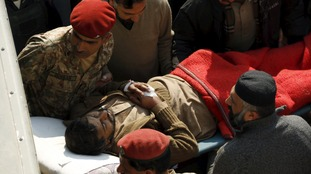 Soldiers and rescue workers move a man, injured in a militant attack at Bacha Khan University
