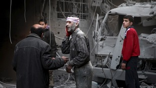 An injured man stands in a site hit by what activists said were Russian airstrikes in Douma, Syria, earlier this month.