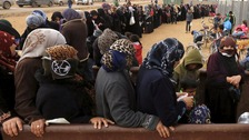 Syrian refugees stand in line as they wait for aid packages