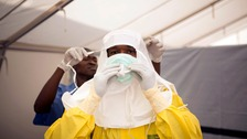 A health worker in Sierra Leone is helped into protective clothing at a treatment centre as the epidemic hit in 2014.