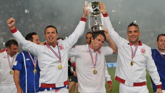 Paddy McGuiness, John Bishop and Robbie Williams celebrate after England&#x27;s victory in the match at Old Trafford for Soccer Aid 2012