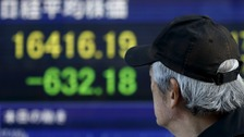 A man walks past an electronic board showing Japan's Nikkei average outside a brokerage in Tokyo