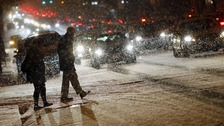 Pedestrians cross the street in freezing conditions ahead of the expected blizzard