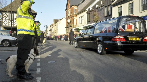 Police with dogs salute as the cortege for Lance Corporal Liam Tasker from the Royal Army Veterinary Corps passes through Wootton Bassett.