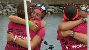 The crew hug after arriving at the end of their epic journey.