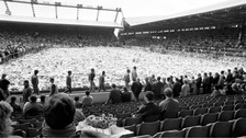Family, friends and fans gather around a pitch full of flowers at Anfield a week after the tragedy in 1989