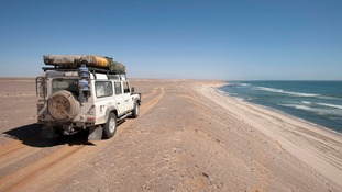 A Land Rover Defender travels on a beach in Namibia.