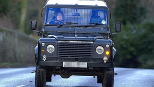 The Queen pictured driving a Land Rover Defender.