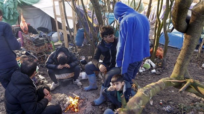 Migrants huddle round a campfire in a camp in France