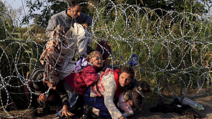 yrian migrants cross under a fence into Hungary at the border with Serbia