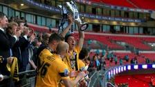 Luke Prosser lifts the League Two play-off trophy.