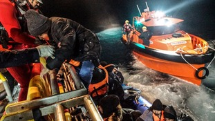 Afghans climb aboard a rescue ship operated by the charity Migrant Offshore Aid Station.