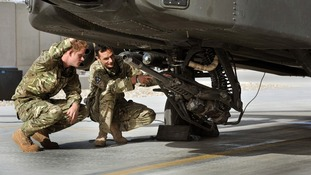 Prince Harry examines the 30mm cannon of an Apache helicopter with a member of his squadron.
