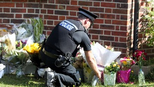 A police officer lays floral tributes from members of the public