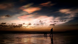 A dog walker on the east coast near Whitley Bay, Northumberland, as rare Nacreous clouds form over the coastline.
