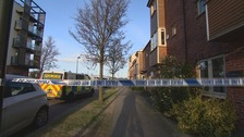Police at the scene where a woman and two children were found dead this morning