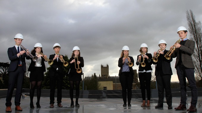 Musicians don hard hats to perform on roof