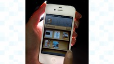 An Apple employee demonstrates the Newsstand app
