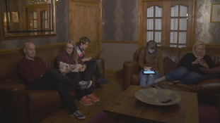 family on sofas with phones