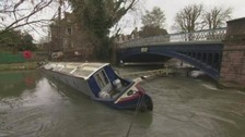 Overturned boat blocks river