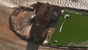 A house in Somerset is seen with high flood defences around the garden