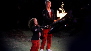 Ellie Simmonds and Jonnie Peacock light their torches from the Paralympic Flame