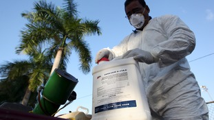 A health worker prepares insecticide before fumigating a neighborhood in San Juan.