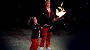 Ellie Simmonds and Jonnie Peacock light their torches from the Paralympic Flame before it is extinguished
