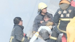 A baby is held by a rescue worker at the site of a collapsed building.