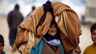 A Syrian woman carries her belongings on her head at a refugee camp near the Bab al-Al Salam crossing.