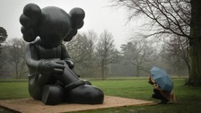 man kneeling in rain with umbrella taking a photo of KAWS sculpture in Yorkshire Sculpture Park