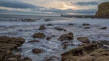 rocks on the shore breaking up the waves, lighthouse in distance at sunrise