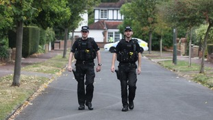 Police walk close to the home of Saad al-Hilli in Claygate, Surrey,