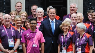 Prime Minister David Cameron poses with some gamesmakers after inviting them to Downing Street