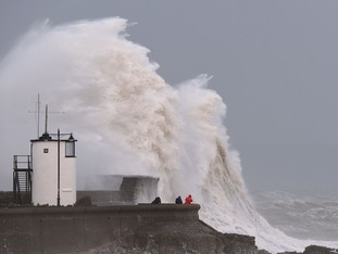 Waves crash high over the sea wall at Porthcawl in Wales as southern Britain was battered by fierce winds and torrential downpours.