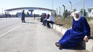 People sit on the pavement as they wait at Turkey's Oncupinar border crossing.
