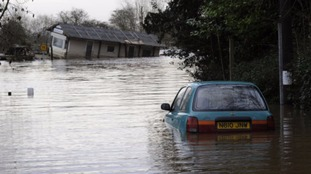A riverside office is left stranded alongside an abandoned car in the middle of floodwater at Acaster Malbis near York.