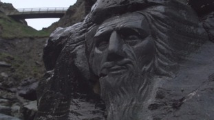 The carved face of Merlin on the beach at Tintagel Castle.