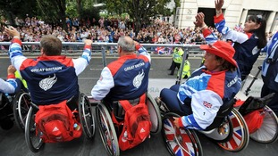 Paralympians wave to the crowd during the athletes parade today
