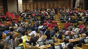 Chaotic scenes in South African parliament as president jeered and opposition MPs walk out