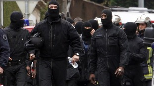 Masked French special unit policemen leave the scene after the assault to capture Mohamed Merah