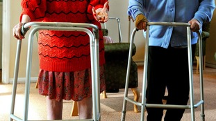 Two elderly residents using zimmer frames